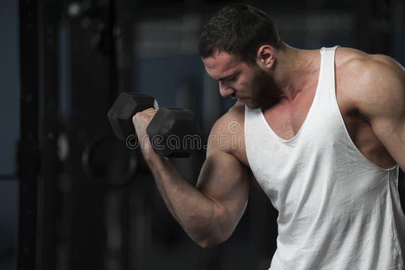Hombre joven atlético fuerte con pesas de gimnasia fotos de archivo libres de regalías