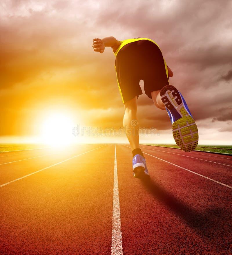 Hombre joven atlético que corre en circuito de carreras con el fondo de la puesta del sol foto de archivo libre de regalías