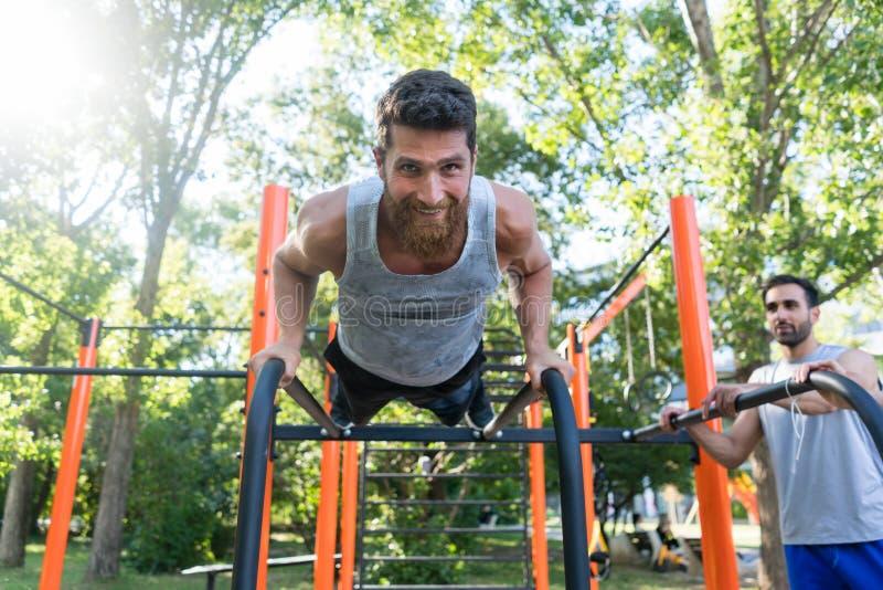 Hombre joven atlético que hace pectorales durante entrenamiento al aire libre en un parque de la aptitud fotos de archivo libres de regalías