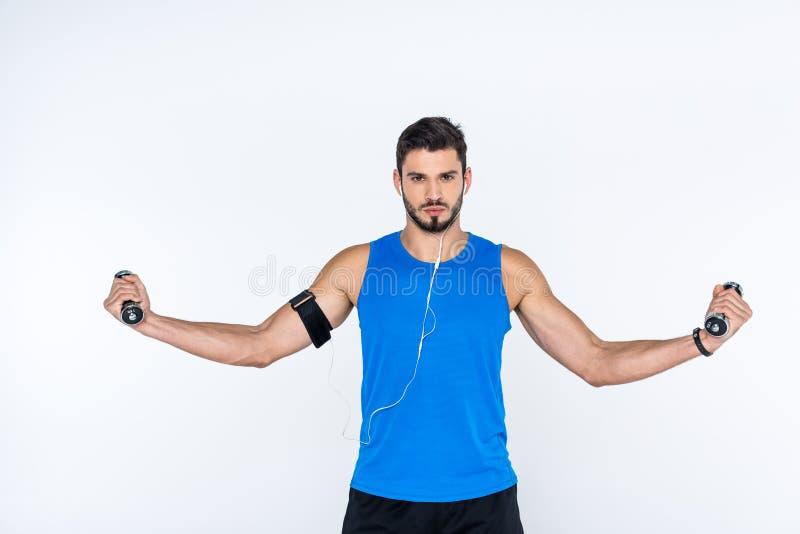 hombre joven atlético que se resuelve con pesas de gimnasia foto de archivo libre de regalías