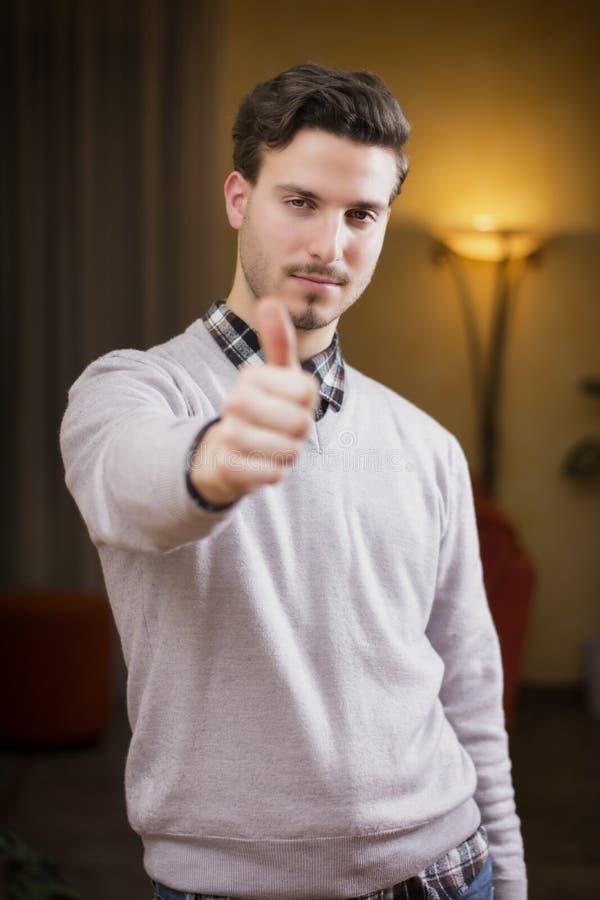 Hombre joven atractivo con el pulgar para arriba que hace la muestra ACEPTABLE imagen de archivo