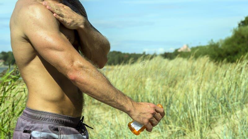 Hombre joven atractivo con el sunblock en la playa fotos de archivo