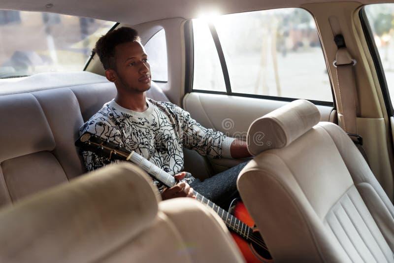 Hombre joven atractivo en coche, en el asiento trasero, en la ropa casual, sosteniendo una guitarra mientras que viaja, durante u fotografía de archivo libre de regalías