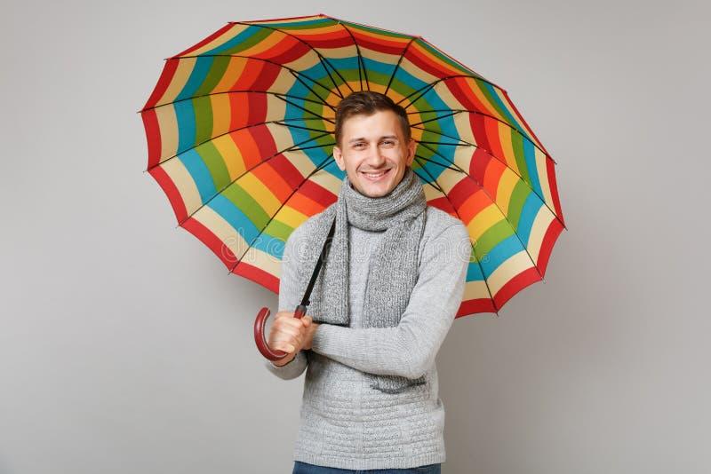 Hombre joven atractivo en el suéter gris, bufanda que sostiene el paraguas colorido aislado en fondo gris en estudio Sano imagen de archivo libre de regalías