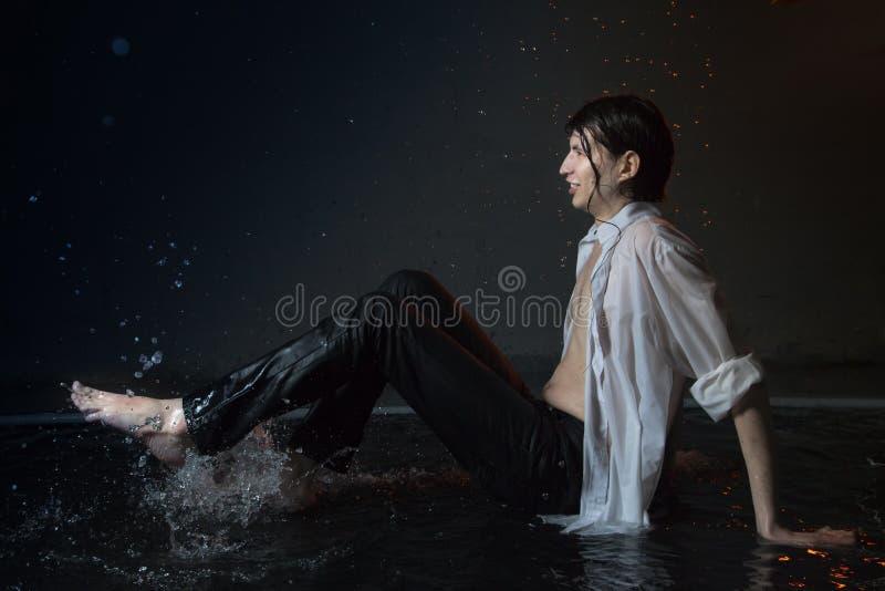 Hombre joven atractivo en la ropa mojada blanca en pequeña piscina bajo gotas de la lluvia Foto del estudio imagen de archivo libre de regalías