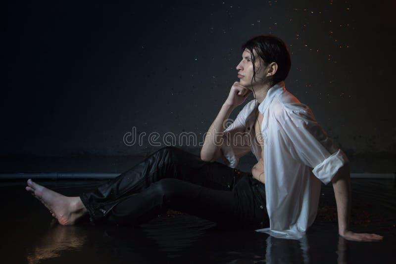 Hombre joven atractivo en la ropa mojada blanca en pequeña piscina bajo gotas de la lluvia Foto del estudio foto de archivo