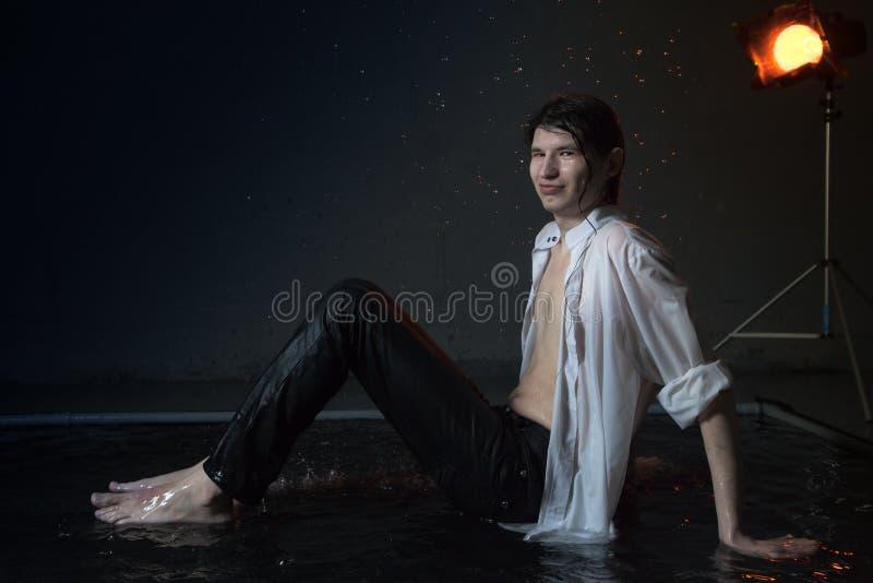 Hombre joven atractivo en la ropa mojada blanca en pequeña piscina bajo gotas de la lluvia Foto del estudio fotografía de archivo