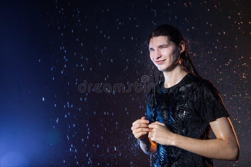 Hombre joven atractivo en ropa mojada negra debajo de la lluvia y del chapoteo del agua, foto del estudio imágenes de archivo libres de regalías