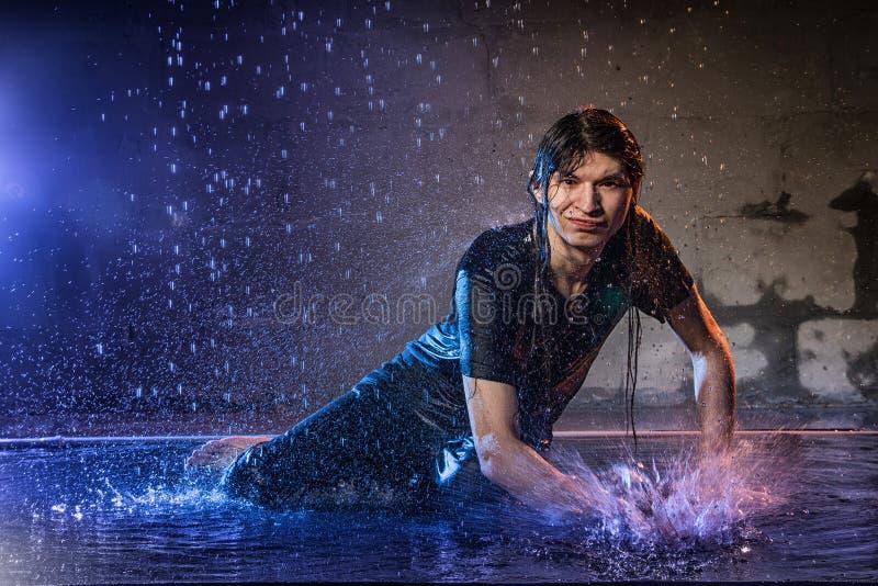 Hombre joven atractivo en ropa mojada negra debajo de la lluvia y del chapoteo del agua, foto del estudio fotos de archivo