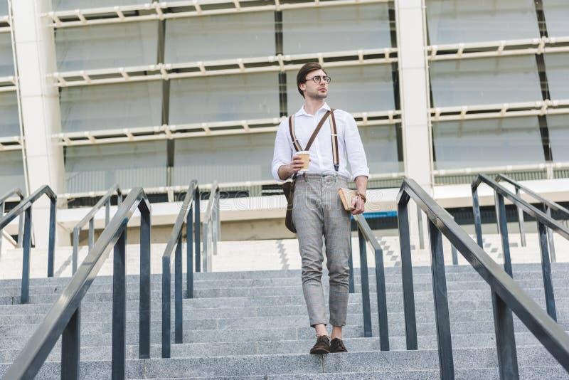 hombre joven atractivo que camina abajo de las escaleras delante del estadio con el libro y el café imagenes de archivo