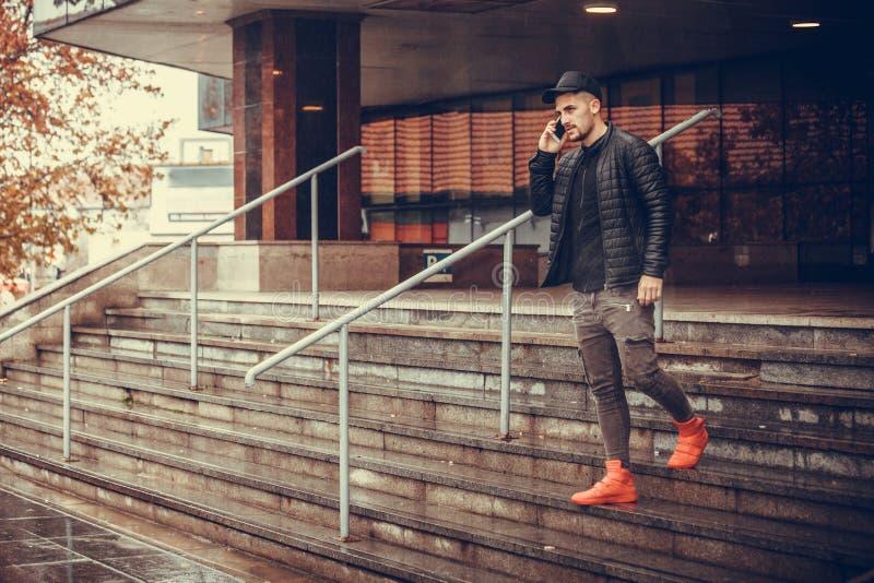 Hombre joven atractivo que camina y que habla en el teléfono móvil imagen de archivo libre de regalías