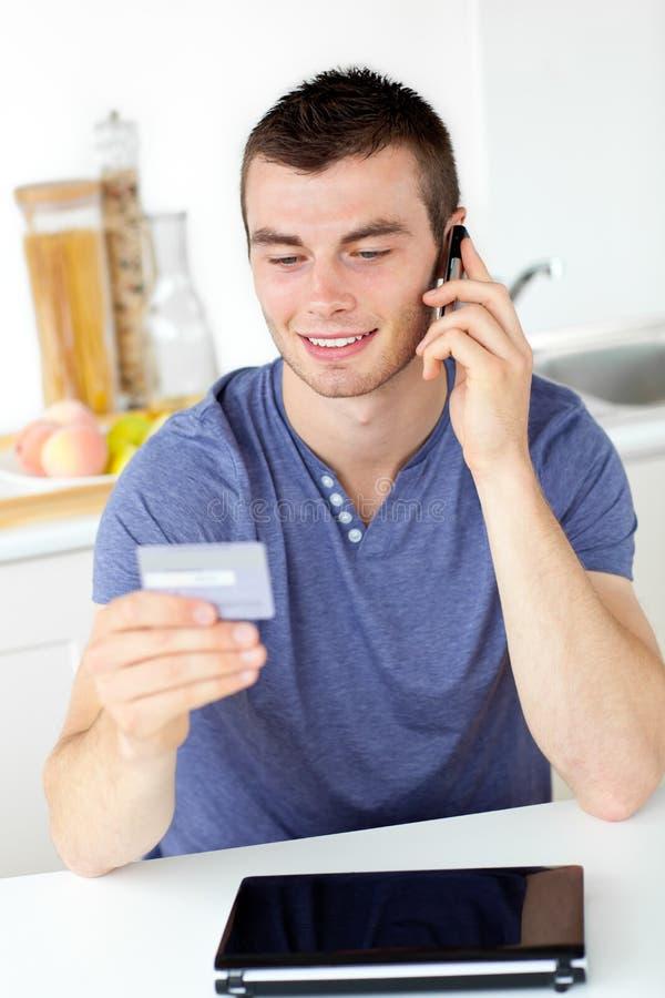 Hombre joven atractivo que habla en tarjeta de la explotación agrícola del teléfono foto de archivo