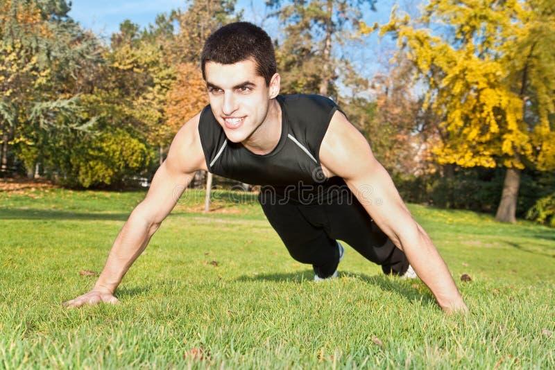 Hombre joven atractivo que hace ejercicio en parque imagen de archivo libre de regalías