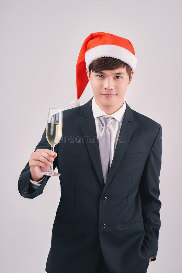 Hombre joven atractivo que lleva el sombrero de santa que sostiene el champán fotos de archivo