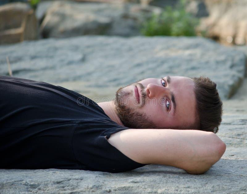 Hombre joven atractivo que miente en su parte posterior en una roca, mirando in camera imagen de archivo