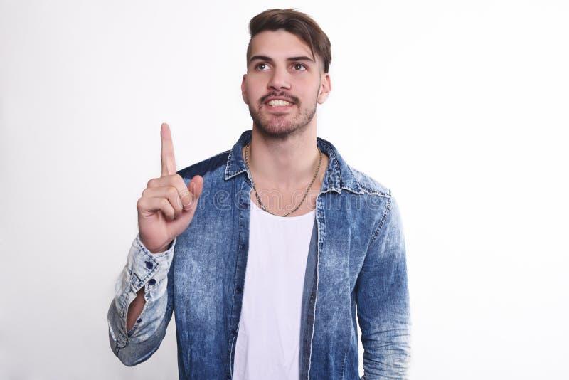 Hombre joven atractivo que señala encima de sorprendido fotos de archivo