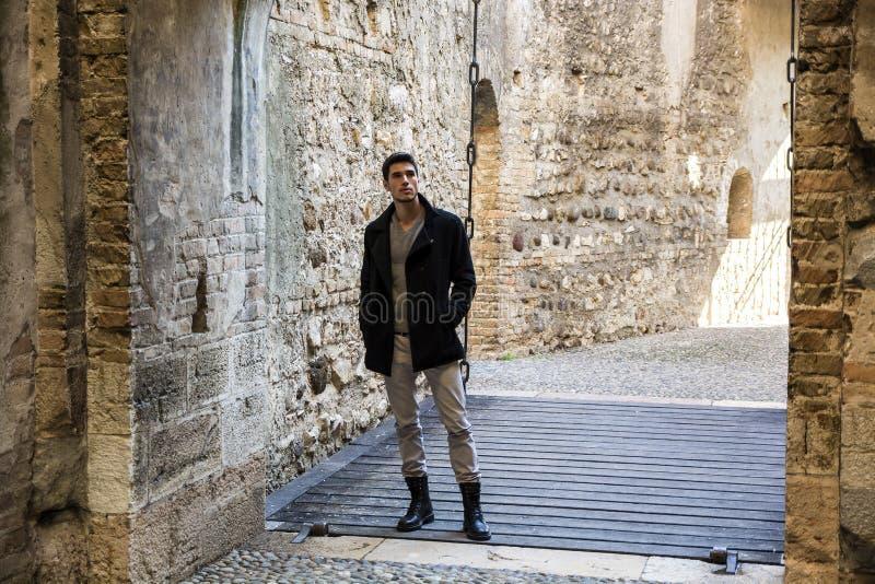 Hombre joven atractivo que se coloca en la entrada del castillo imagen de archivo libre de regalías