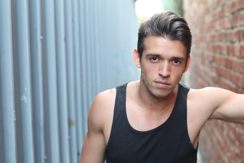 Hombre joven atractivo que se opone a la pared urbana del pasillo colorido, mirando la cámara foto de archivo