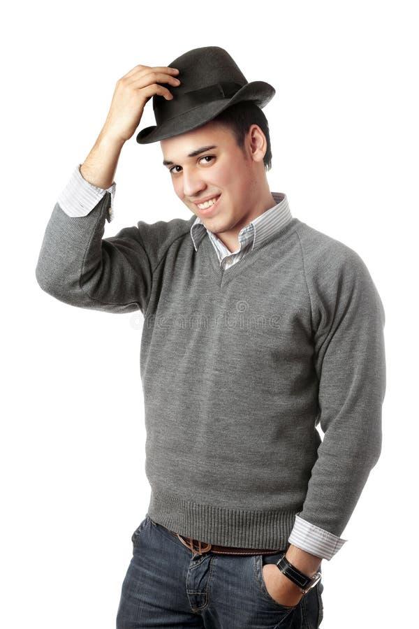 Hombre joven atractivo sonriente que desgasta el sombrero negro
