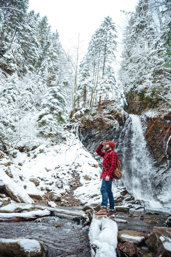 Hombre joven barbudo atractivo que camina cerca de la cascada de la montaña en invierno imagenes de archivo