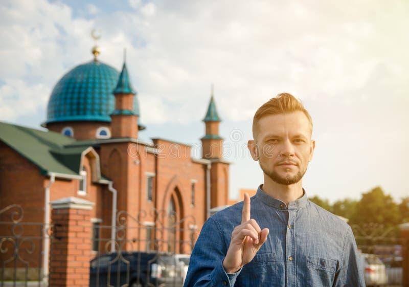 Hombre joven barbudo con el dedo índice aumentado cerca de la mezquita fotografía de archivo libre de regalías