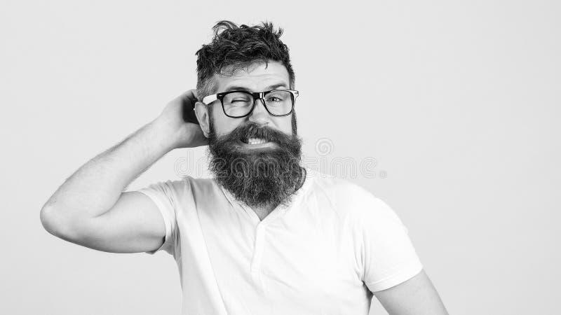 Hombre joven barbudo confuso en vidrios Inconformista que intenta solucionar problema difícil El individuo barbudo intenta recole fotos de archivo libres de regalías