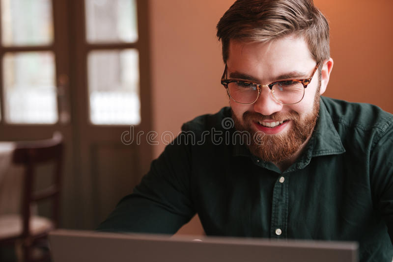 Hombre joven barbudo feliz que usa el ordenador portátil fotografía de archivo