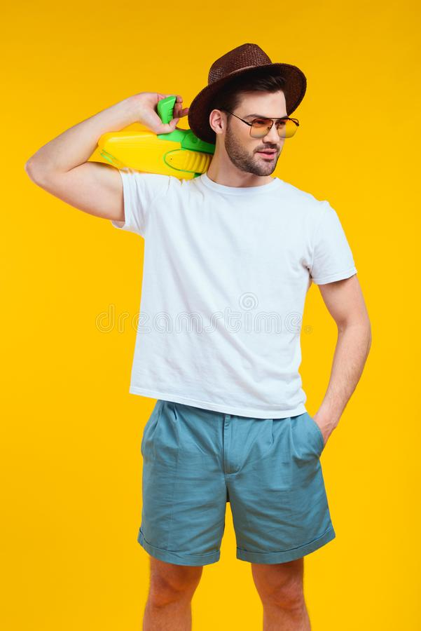 hombre joven barbudo hermoso en el equipo del verano que sostiene el arma de agua y que mira lejos fotografía de archivo