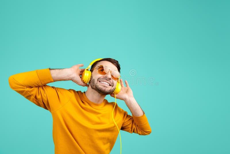 Hombre joven barbudo hermoso que lleva las gafas de sol amarillas que escuchan la música con los auriculares amarillos en fondo c foto de archivo