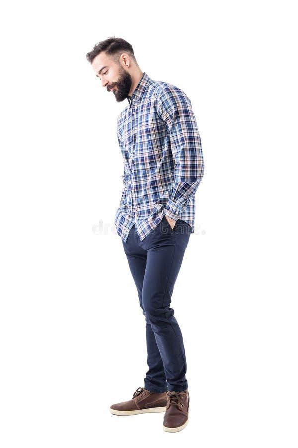 Hombre joven barbudo hermoso tímido en camisa de tela escocesa con las manos en bolsillos que sonríe y que mira abajo foto de archivo