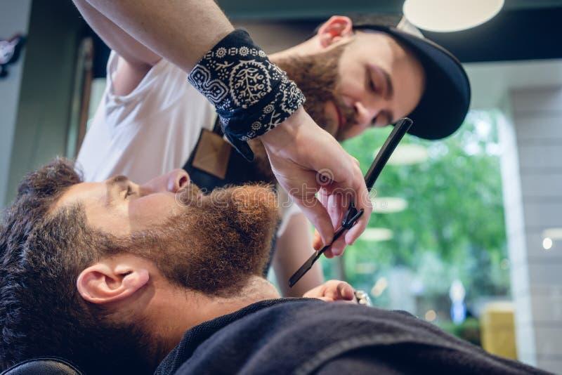 Hombre joven barbudo listo para afeitar en el salón de pelo de un peluquero experto imagenes de archivo