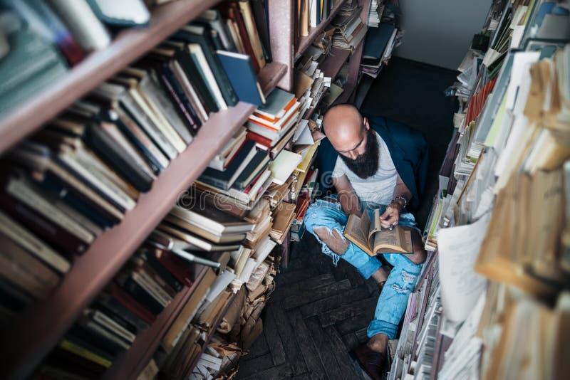 Hombre joven barbudo que lee un libro que se sienta en el piso entre a imagenes de archivo