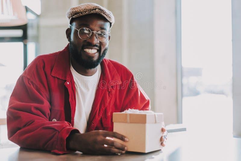 Hombre joven barbudo que se sienta con la caja y la sonrisa de regalo imagenes de archivo