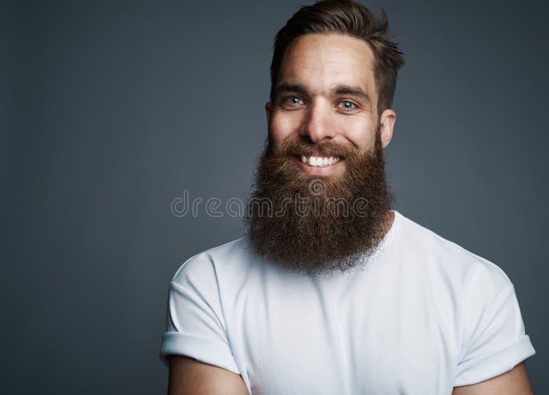 Hombre joven barbudo que sonríe contra un fondo gris fotografía de archivo
