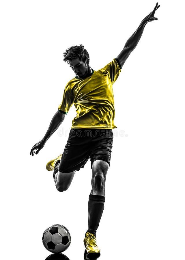 Hombre joven brasileño del futbolista del fútbol que golpea la silueta con el pie fotografía de archivo