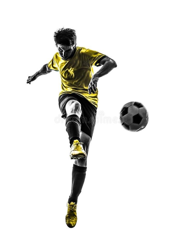 Hombre joven brasileño del futbolista del fútbol que golpea la silueta con el pie fotografía de archivo libre de regalías