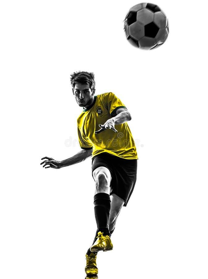 Hombre joven brasileño del futbolista del fútbol que golpea la silueta con el pie foto de archivo libre de regalías
