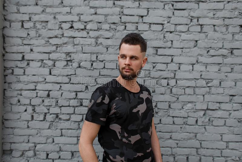 Hombre joven brutal atractivo en una camiseta militar de moda fotos de archivo libres de regalías