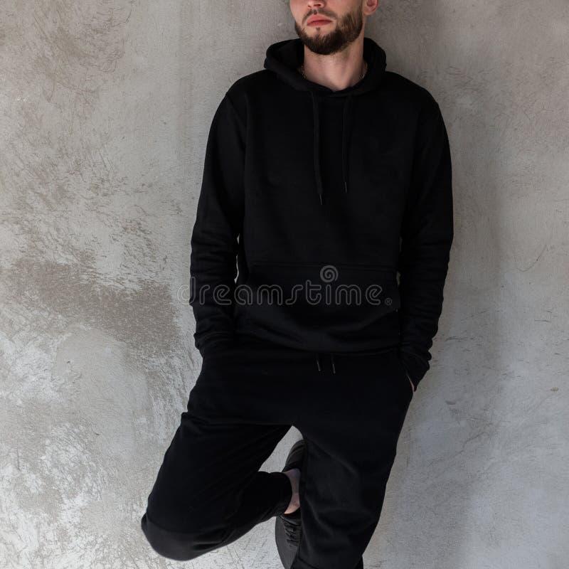 Hombre joven brutal atractivo en una camiseta negra de moda en vaqueros negros del vintage con una barba elegante que presenta en foto de archivo