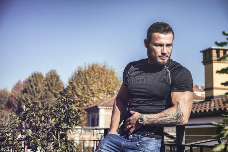 Hombre joven cabelludo oscuro hermoso que mira hacia fuera en la visión foto de archivo
