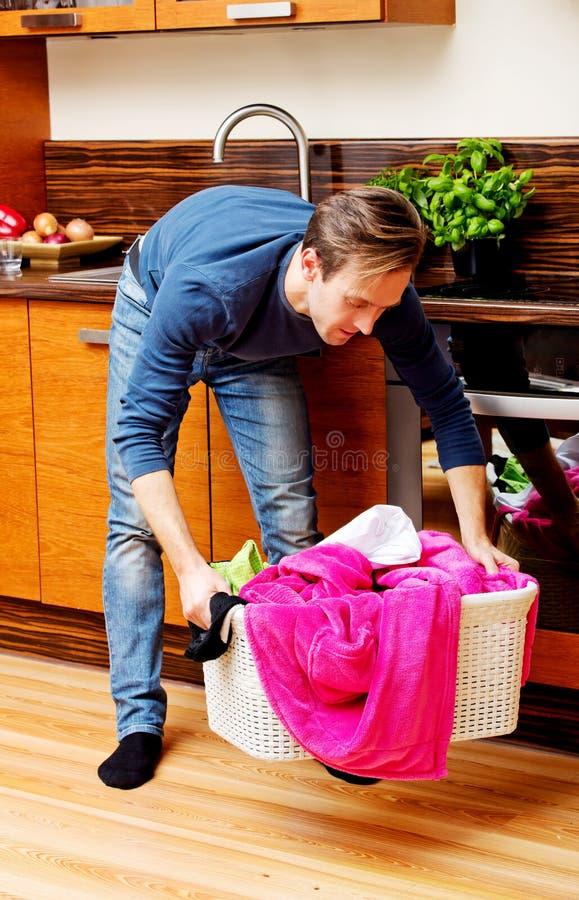 Hombre joven cansado con la cesta de lavadero imágenes de archivo libres de regalías