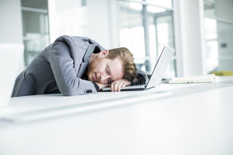 Hombre joven cansado en la oficina foto de archivo