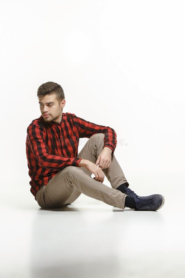 Hombre joven casual que se sienta en el piso y que mira a un lado, lejos de la cámara, en un fondo blanco imagen de archivo
