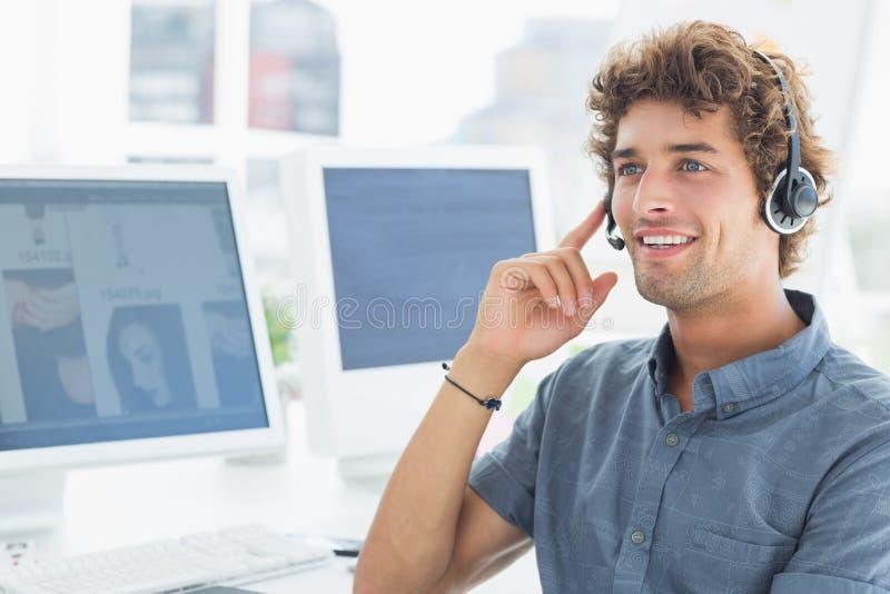 Hombre joven casual sonriente con las auriculares en oficina fotografía de archivo