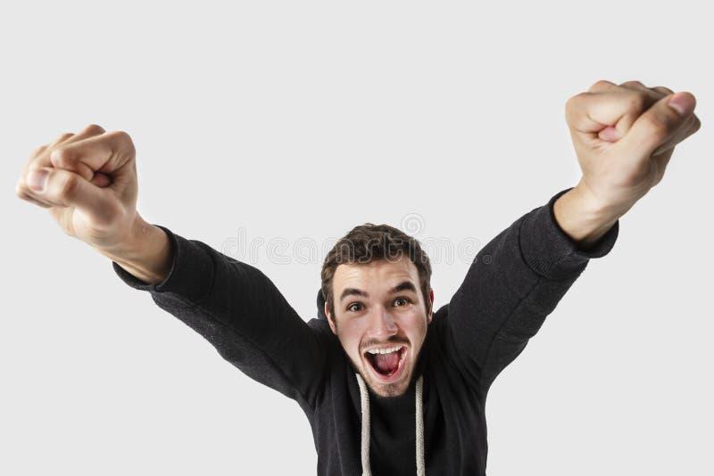Hombre joven caucásico extático que mira en la cámara Aislado en el fondo blanco fotografía de archivo