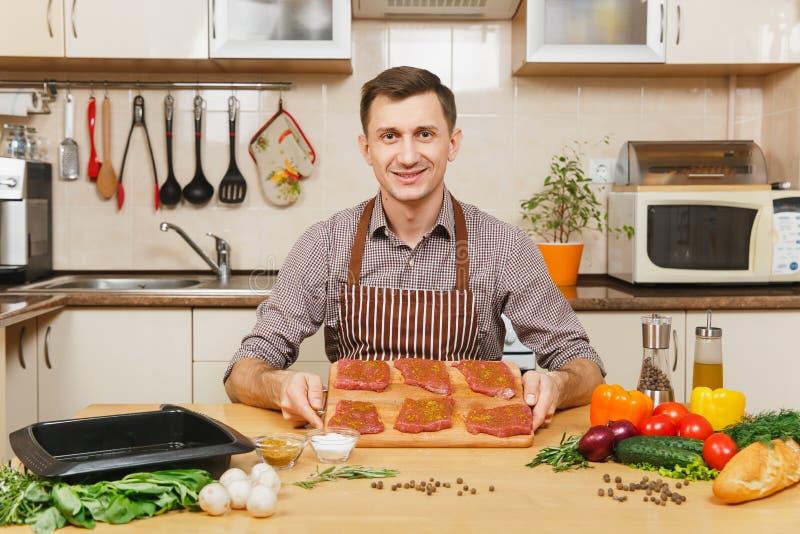 Hombre joven caucásico hermoso, sentándose en la tabla Forma de vida sana El cocinar en el país Prepare el alimento imagen de archivo libre de regalías