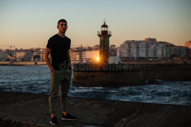 Hombre joven cerca del faro del mar en la 'promenade' fotos de archivo