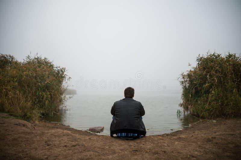 Hombre joven cerca del lago fotografía de archivo