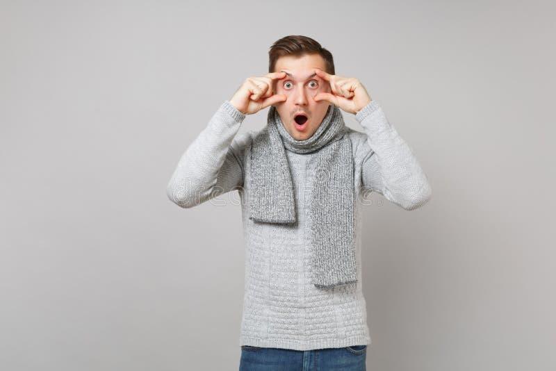 Hombre joven chocado en el suéter gris, bufanda que mantiene la boca abierta de par en par, estirando los párpados en fondo gris fotografía de archivo libre de regalías