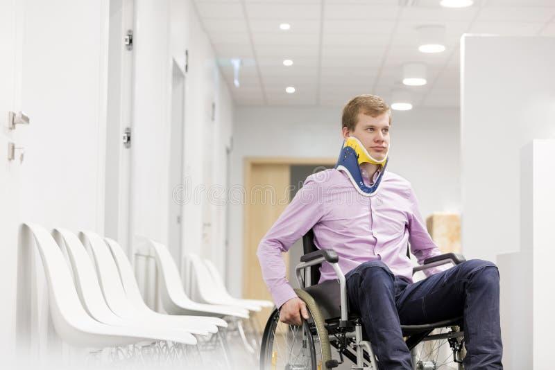 Hombre joven con el apoyo de cuello que se sienta en la silla de ruedas en el pasillo del hospital fotos de archivo libres de regalías